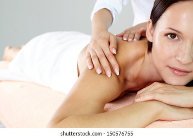 Pretty brunette enjoying the procedure of massage