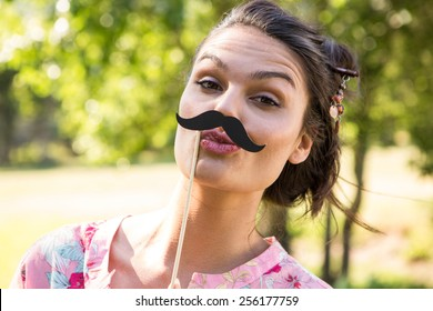 Pretty brunette with fake mustache on a summers day