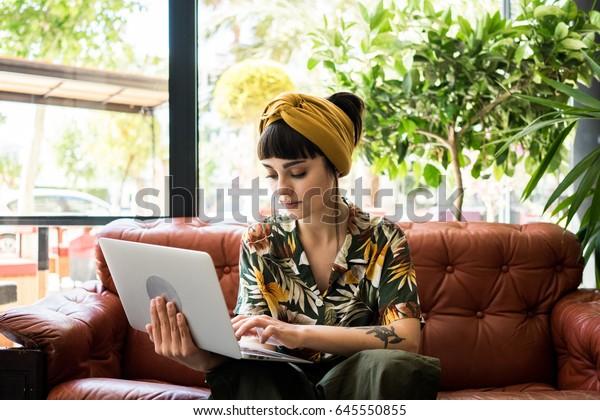 Довольно брюнетка девушка проверяет свою почту на маленьком портативном ноутбуке, ожидая ее заказа в кафе магазине. Она путешествует во время летних каникул и иногда работает дистанционно