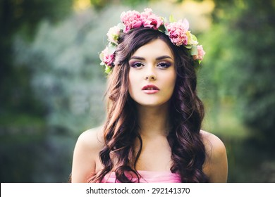 Pretty Brunette Girl with Curly Hairstyle Outdoors. Fashion Woman in Park. Makeup, Dark Wave Hair, Flowers