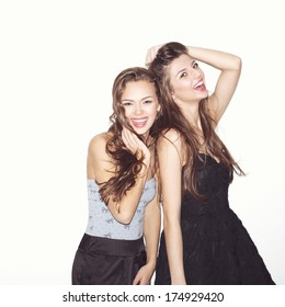 Pretty brunette girl friends having fun. Both looking at camera and smiling (laughing). Festive mood. Inside