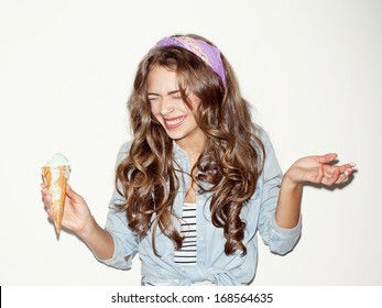 Pretty brunette girl having fun and eating ice cream. Closed eyes, smiling. Indoors, lifestyle