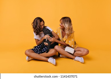 Pretty brunette girl kissing french bulldog. Indoor photo of two best friends posing with cute black puppy.