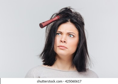 Pretty brunette girl making funny faces with comb in hair isolated on a white background
