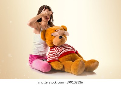 Pretty brunette girl with pajamas covering his eyes on ocher background