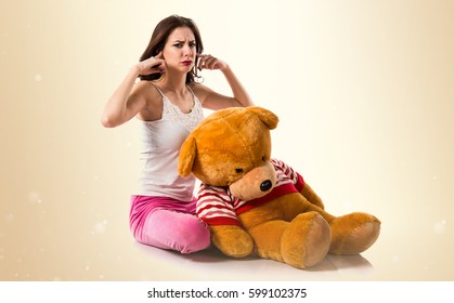Pretty brunette girl with pajamas covering his ears on ocher background
