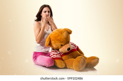 Pretty brunette girl with pajamas covering his mouth on ocher background