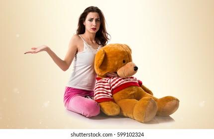 Pretty brunette girl with pajamas having doubts on ocher background