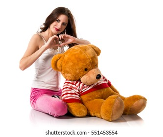 Pretty brunette girl with pajamas making a heart with his hands