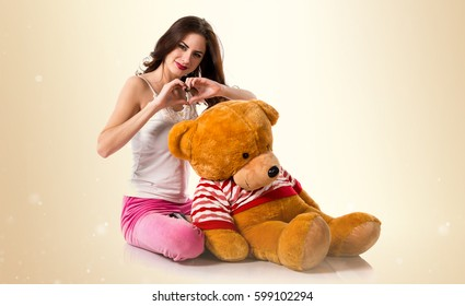 Pretty brunette girl with pajamas making a heart with his hands on ocher background