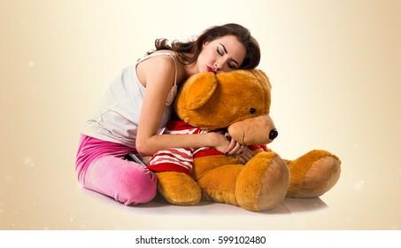 Pretty brunette girl with pajamas sleeping on ocher background
