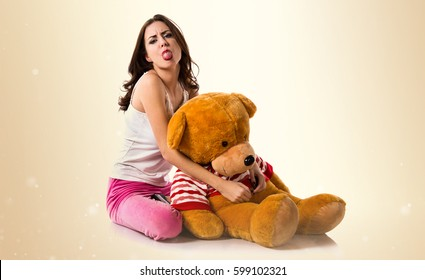 Pretty brunette girl with pajamas taking out his tongue on ocher background