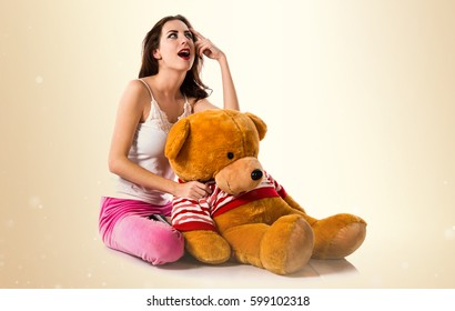 Pretty brunette girl with pajamas thinking on ocher background