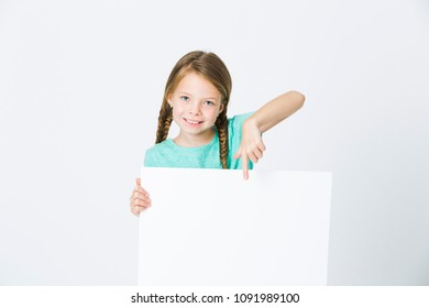 pretty, brunette girl is pointing at white board in front of white background