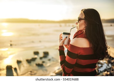 Pretty brunette girl walk outdoor in the park with coffee