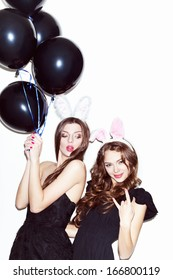 Pretty brunette girls with bunny ears and pink lips having fun. One showing sing by her hand, looking at camera. Second holding black balloons. Inside
