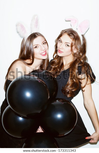Pretty brunette girls with bunny ears and pink lips having fun. Keeping black balloons in their hands. Wearing dresses. Looking at camera. Inside