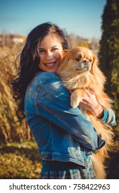 Pretty brunette hair young woman on a walk with friend little nice red dog pekingese. Lady of dog lover and pets. Dog owner with lovely pet