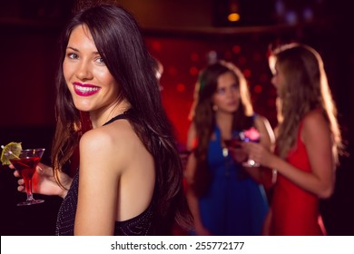 Pretty brunette having a cocktail at the nightclub