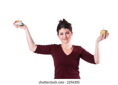 Pretty brunette holding up two apples as if on a measuring scale
