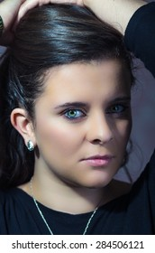 pretty brunette with intense eyes closeup looking into camera with serious expression