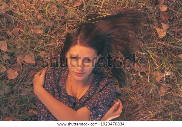 Pretty brunette lady relaxing on the autumnal grass in the park and looking at camera.