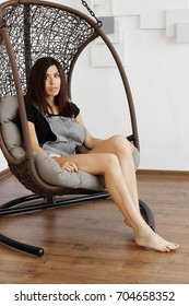 A pretty brunette with long slender legs and sharp knees sits in a stylish wicker chair. beautiful girl by nature. Beauty in a hanging chair rocking chair. girl with a soft tan and velvet skin