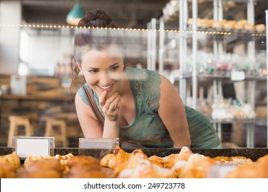 Pretty brunette looking at pastrys at the bakery
