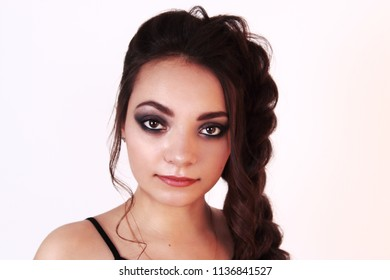 Pretty brunette with make-up and braid poses in white studio, close up