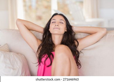 Pretty brunette relaxing on the couch at home in the living room