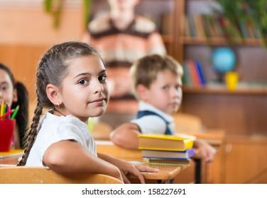 Pretty brunette schoolgirl during lesson at school