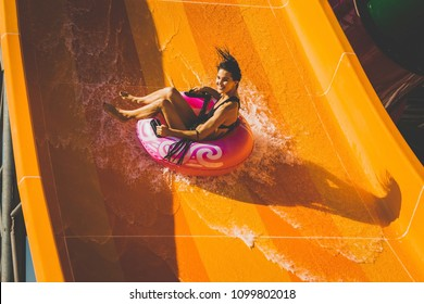 pretty brunette slim woman on the rubber ring having fun going down on the orange water slide in the aqua park. Summer Vacation. Weekend on resort