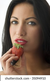 pretty brunette with a strawberry near her mouth with red lips