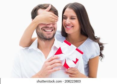 Pretty brunette surprising boyfriend with a gift on white background