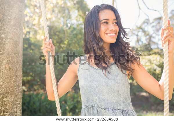 Pretty brunette swinging in park on a sunny day