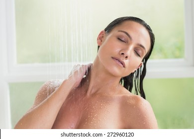 Pretty brunette taking a shower in a bathroom