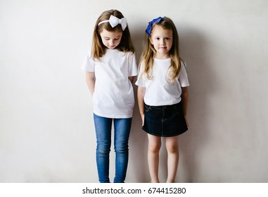 Pretty brunette two child girls in white t-shirts and blue jeans and skirt with long hair, look at camera and down on tshirt