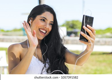 Pretty brunette using headphones and waving at camera of smartphone having videocall while chilling in summer park.