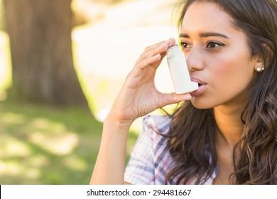Pretty brunette using inhaler on a sunny day