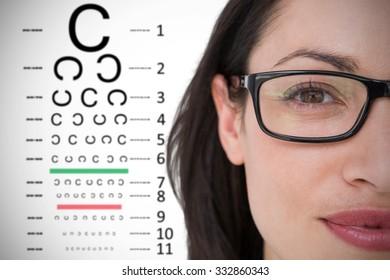 Pretty brunette wearing eye glasses against eye test