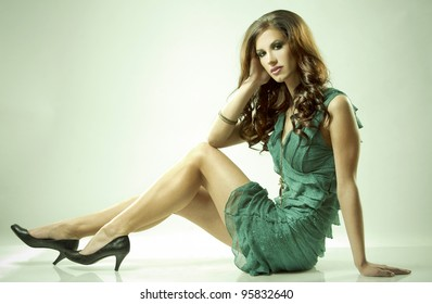 pretty brunette wearing green fashion dress on light background