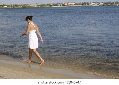 Pretty Brunette in white dress walking along the shore