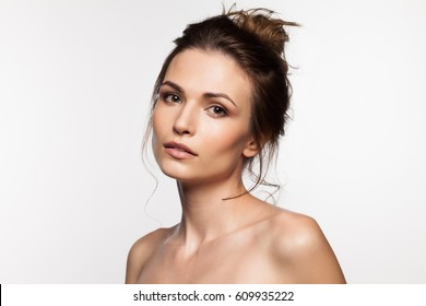 Pretty brunette woman with bare shoulders on a white background
