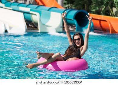 hübsche brunette Frau in schwarzem Bikini auf dem aufblasbaren Ring im Pool. Sommerurlaub. Genießen Sie die Sonne. Wochenende im Resort und Spa