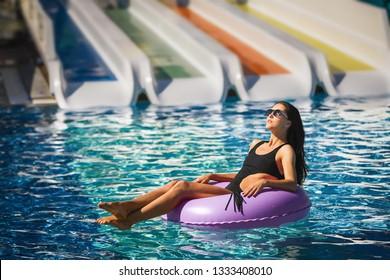 pretty brunette woman in black bikini on the inflatable ring in the swimming pool. Summer Vacation. Enjoying suntan. Weekend on resort