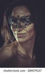 Pretty brunette woman in black mask metal frills