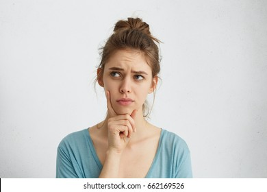Pretty brunette woman with blue eyes and pinned-up hair frowning her eyebrow while looking aside with placid and thoughtful look. Pensive female with puzzled expression thinking something over