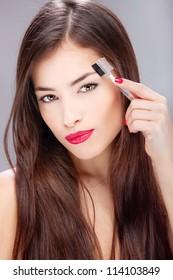 Pretty brunette woman combing her eyebrow