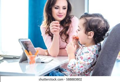 Pretty brunette woman feeding her daughter