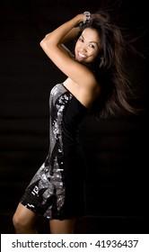 pretty brunette woman having fun on black background
